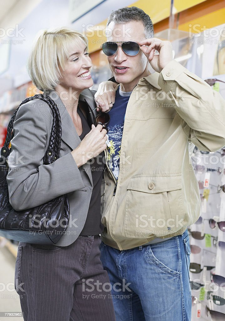 Couple trying on sunglasses in store royalty-free stock photo