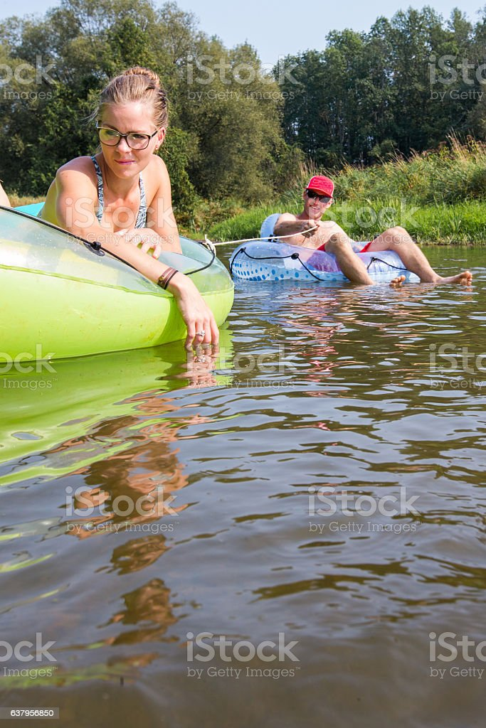 Couple tubing down the river in the summer stock photo