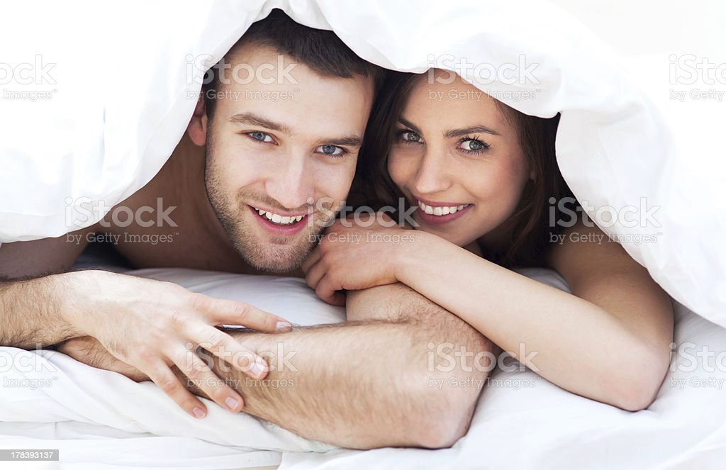 Couple under bed covers royalty-free stock photo
