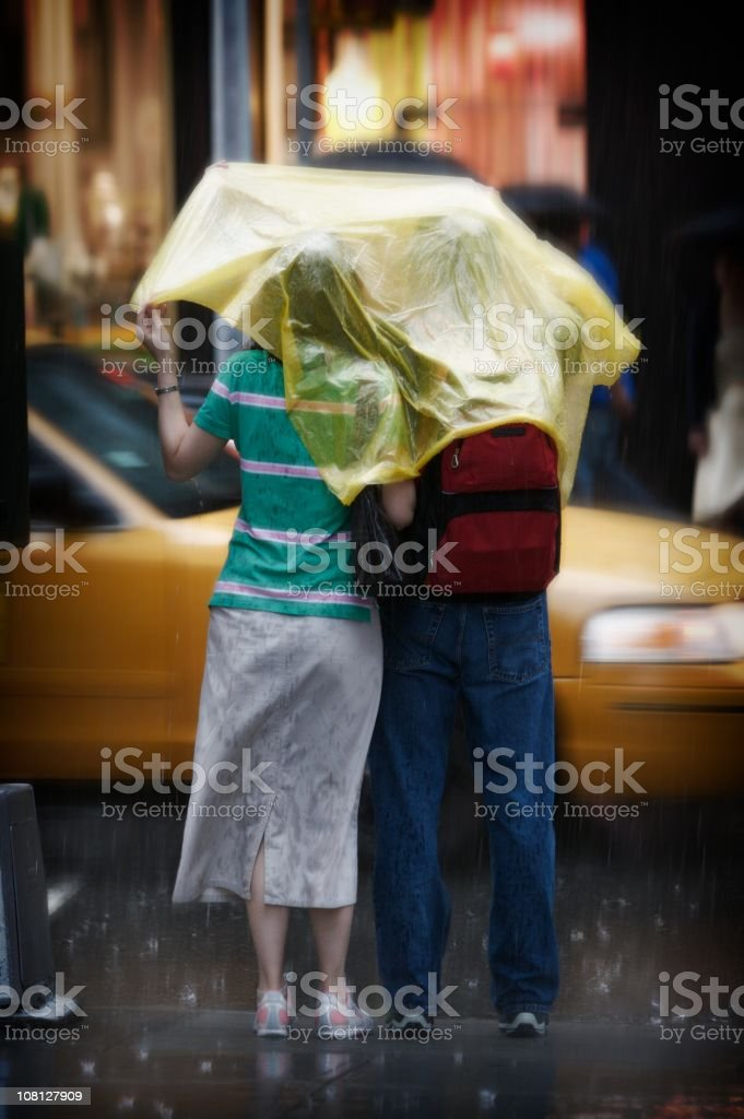 Couple under one cover in the rain stock photo
