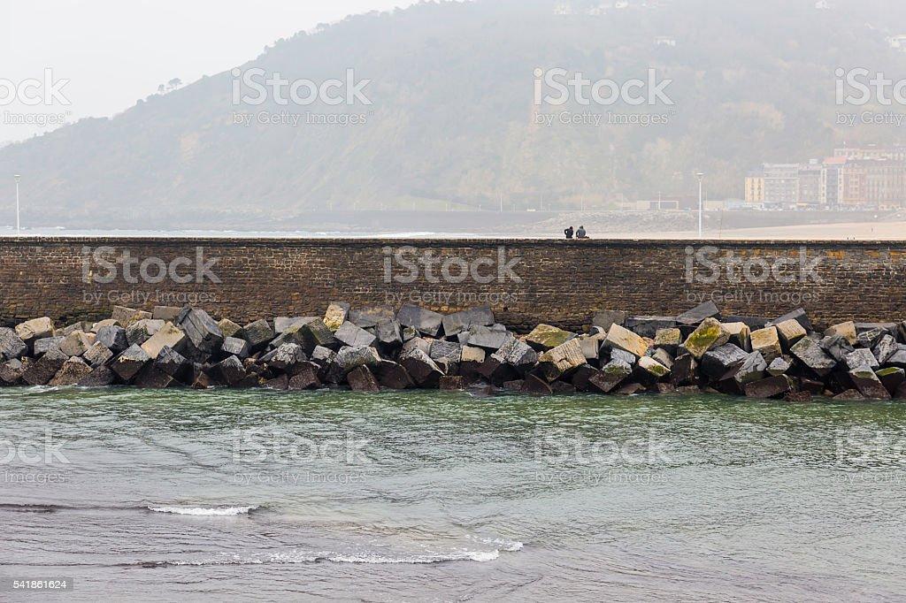 couple under rain close to the sea stock photo