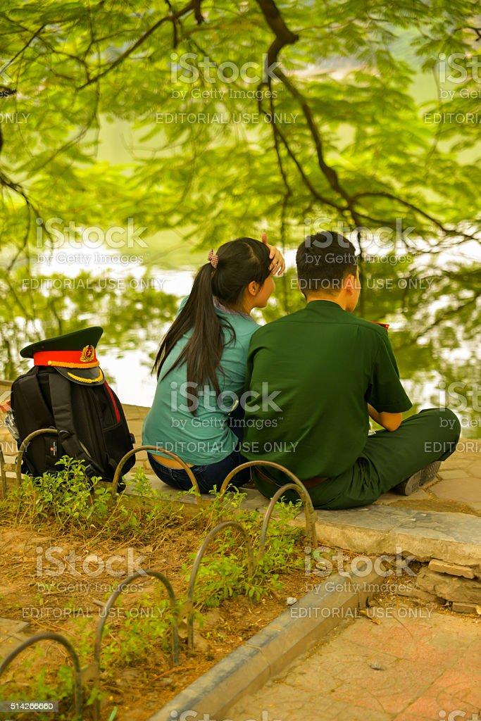 Couple Under Tree On Hoan Kiem Lake in Hanoi, Vietnam. stock photo