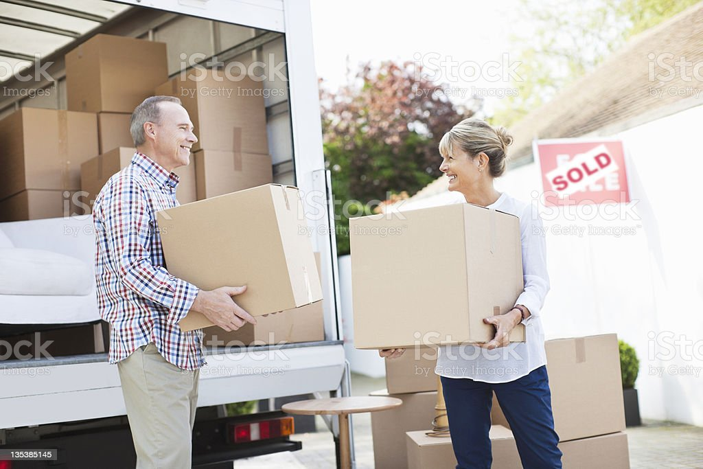 Couple unloading boxes from moving van royalty-free stock photo
