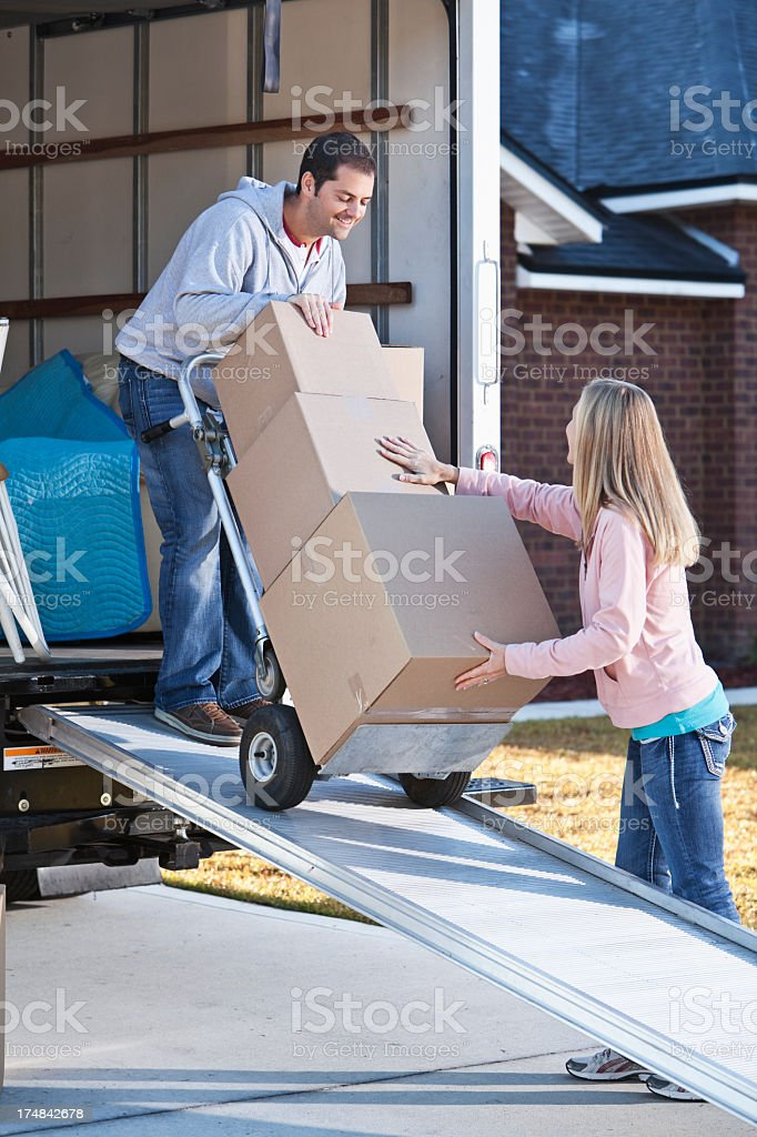 Couple unloading boxes from moving van stock photo