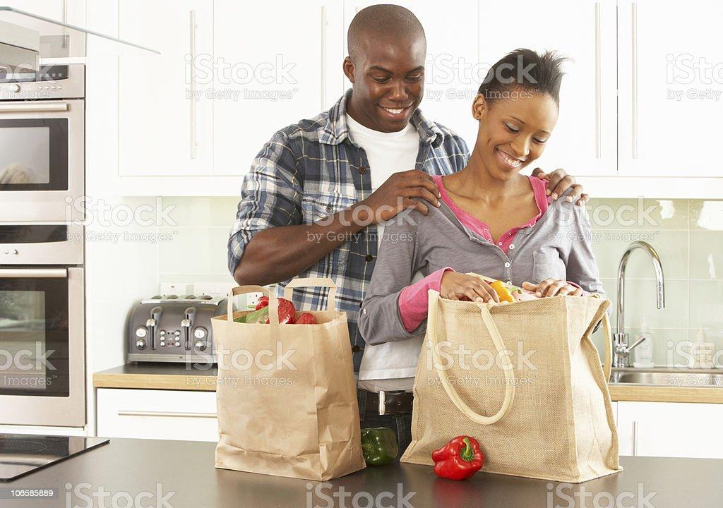Couple Unpacking Shopping In Modern Kitchen stock photo