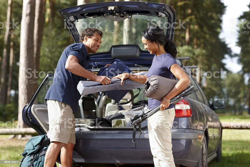 Couple unpacking their car on camp site stock photo