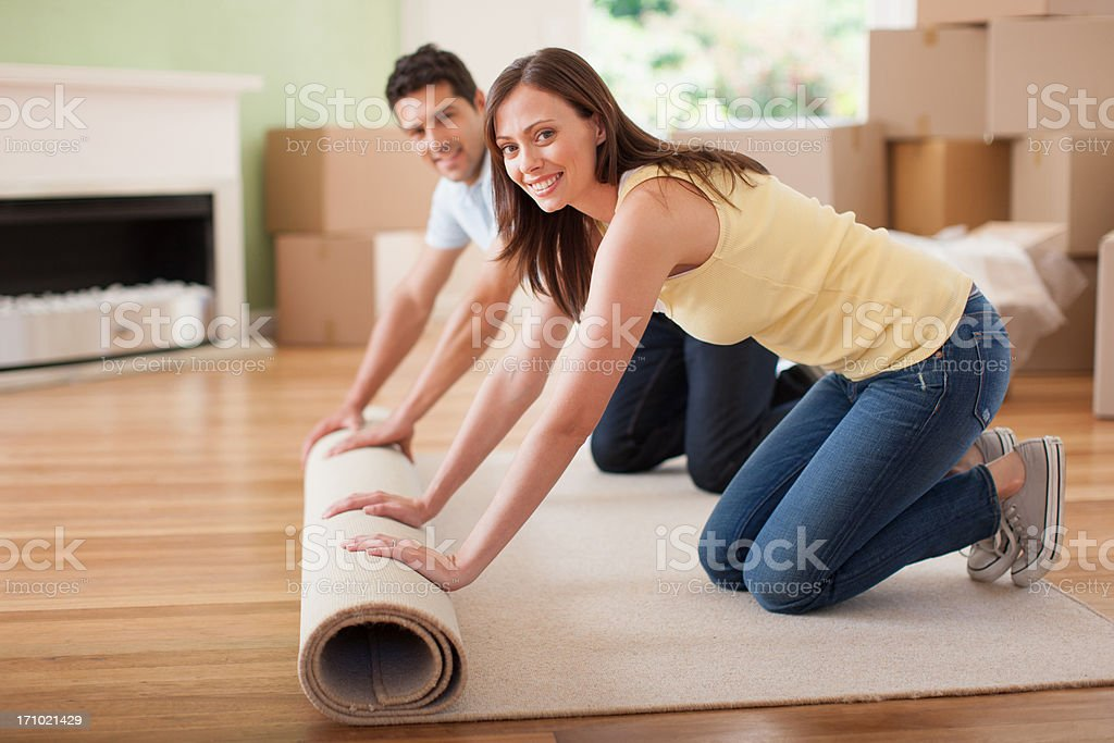 Couple unrolling carpet in new house stock photo