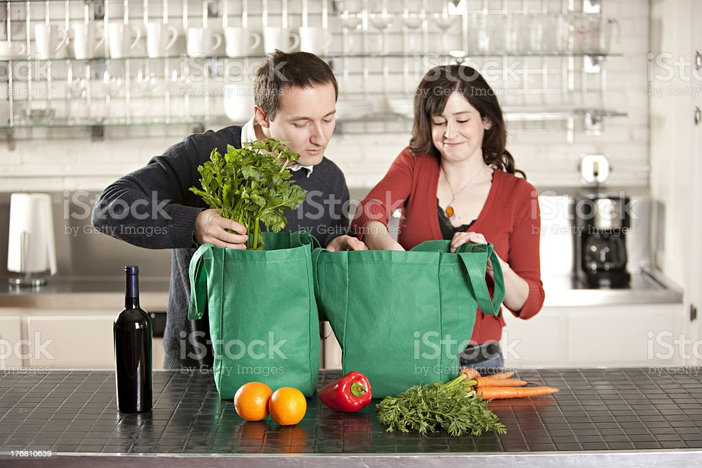 Couple Uses Recycle Grocery Bags in the Kitchen stock photo