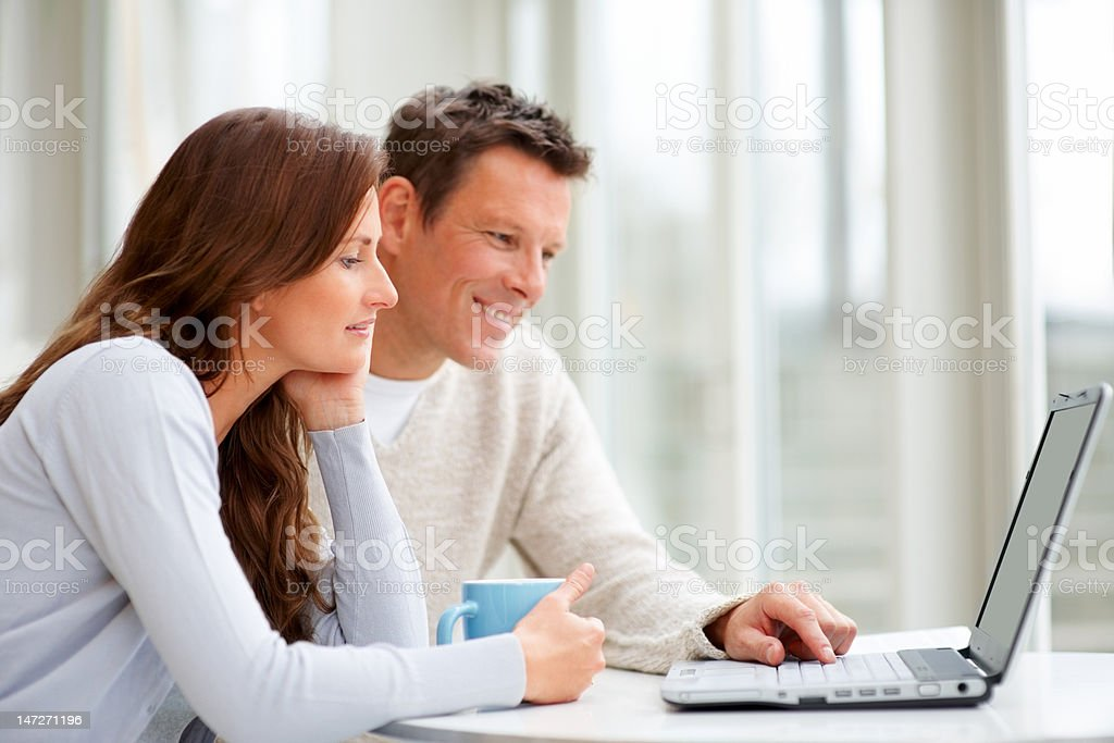 Couple using a laptop and smiling royalty-free stock photo