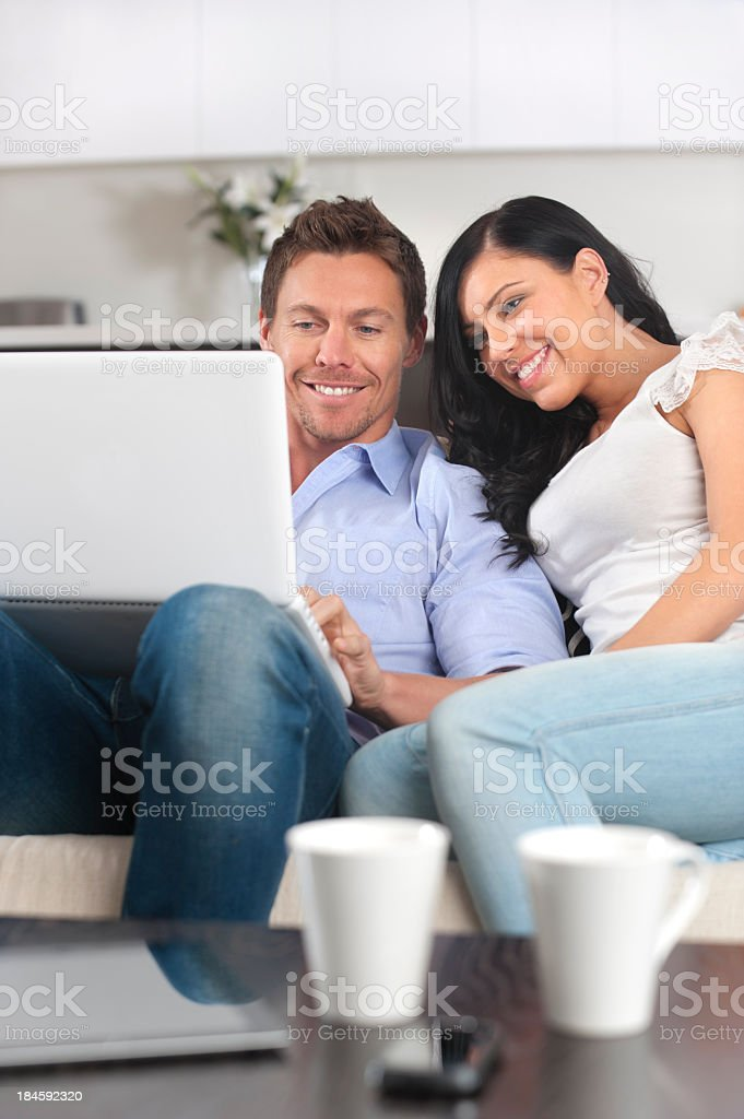 Couple using a laptop computer together on the sofa royalty-free stock photo