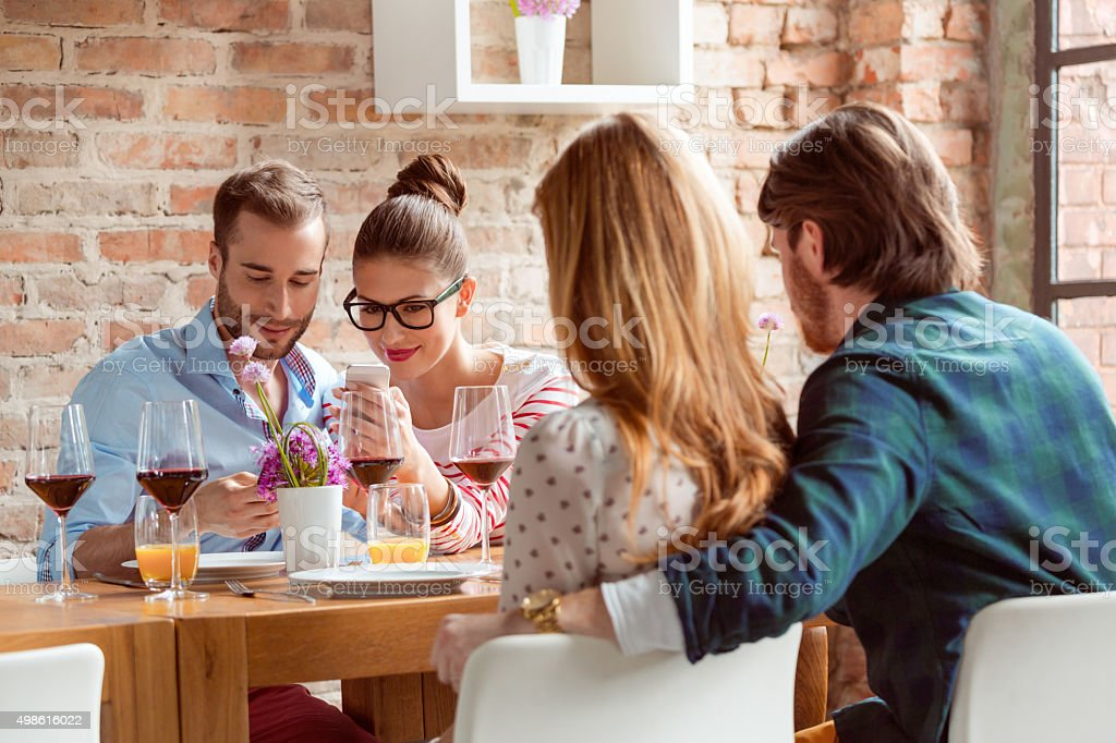 Couple using a smart phones during lunch in the restaurant stock photo