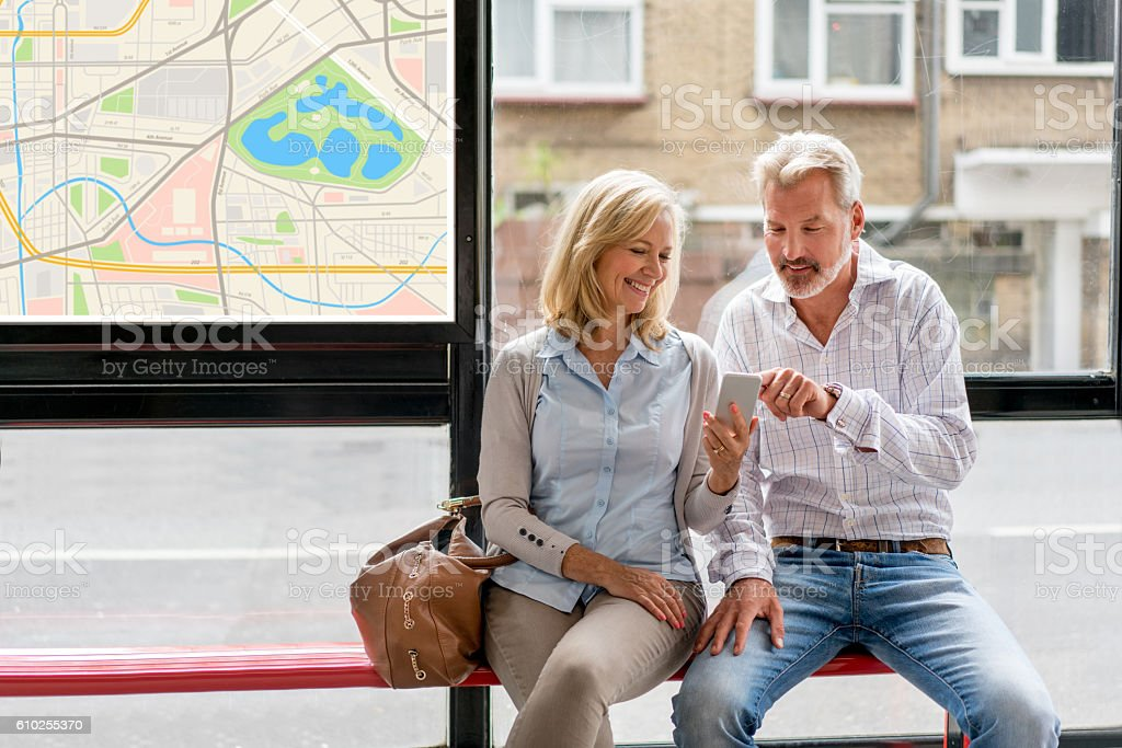 Couple using cell phone app at a bus station stock photo