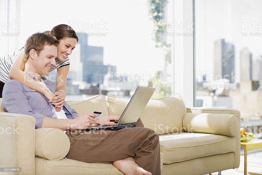 Couple using credit card to purchase merchandise on internet stock photo