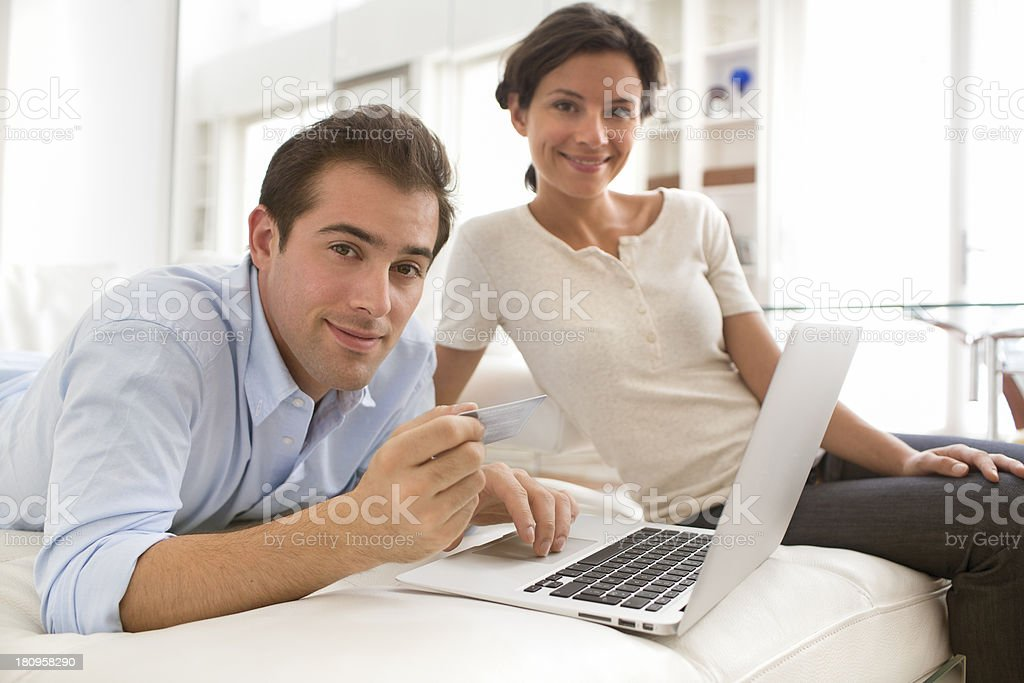 Couple using credit card to shop online, looking camera royalty-free stock photo