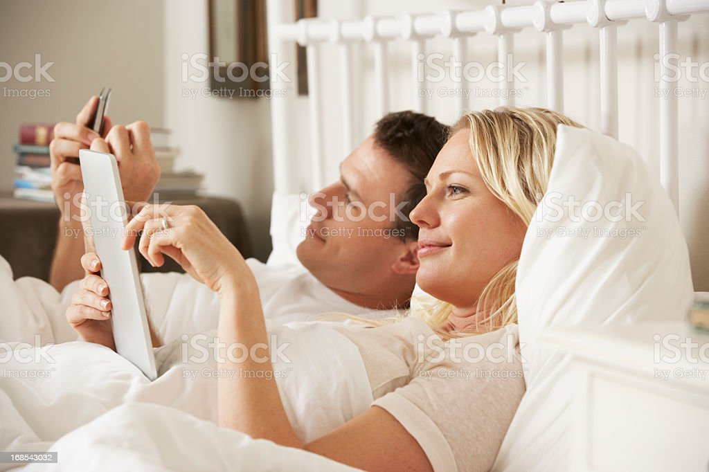 Couple Using Digital Tablet And Mobile Phone In Bed royalty-free stock photo