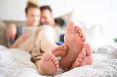 Couple using digital tablet in bed, close up on feet