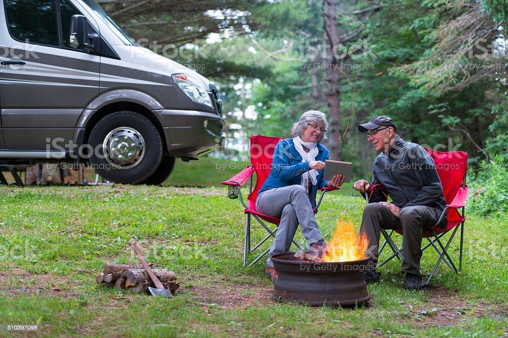 Couple using digital tablet near campfire stock photo