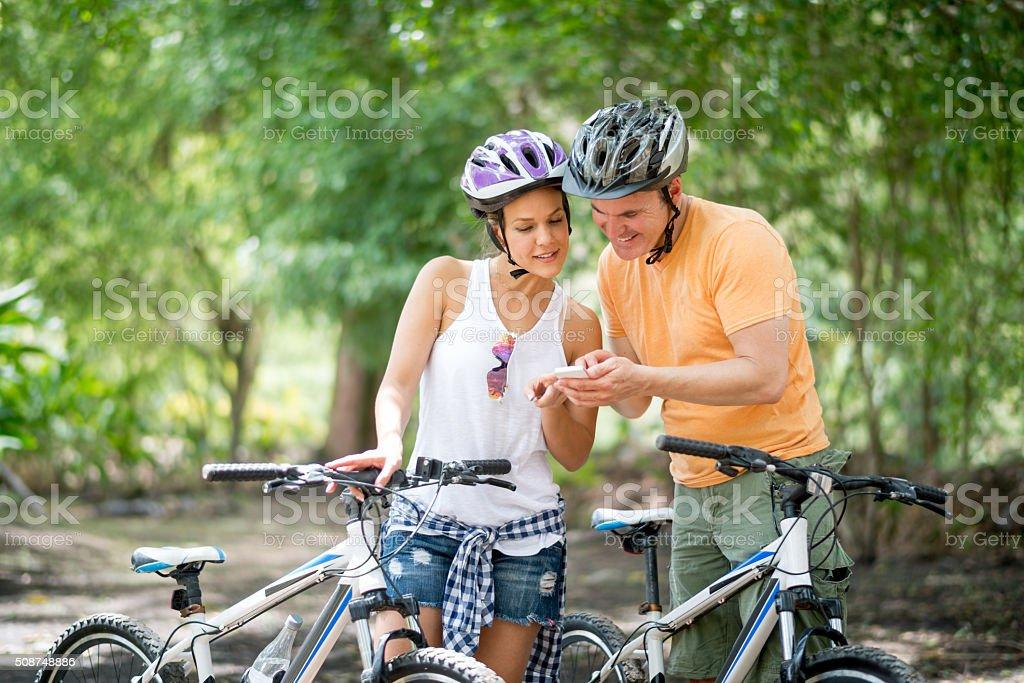 Couple using GPS while mountain biking stock photo