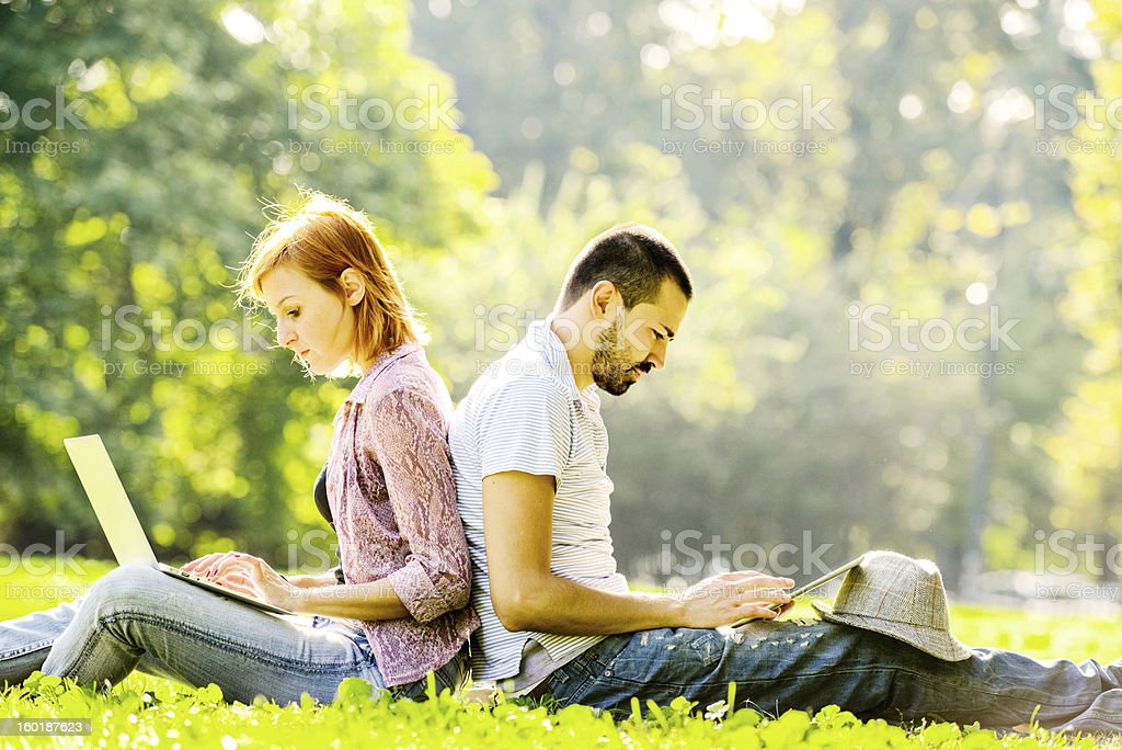 Couple Using Laptop and Digital Tablet Outdoors stock photo