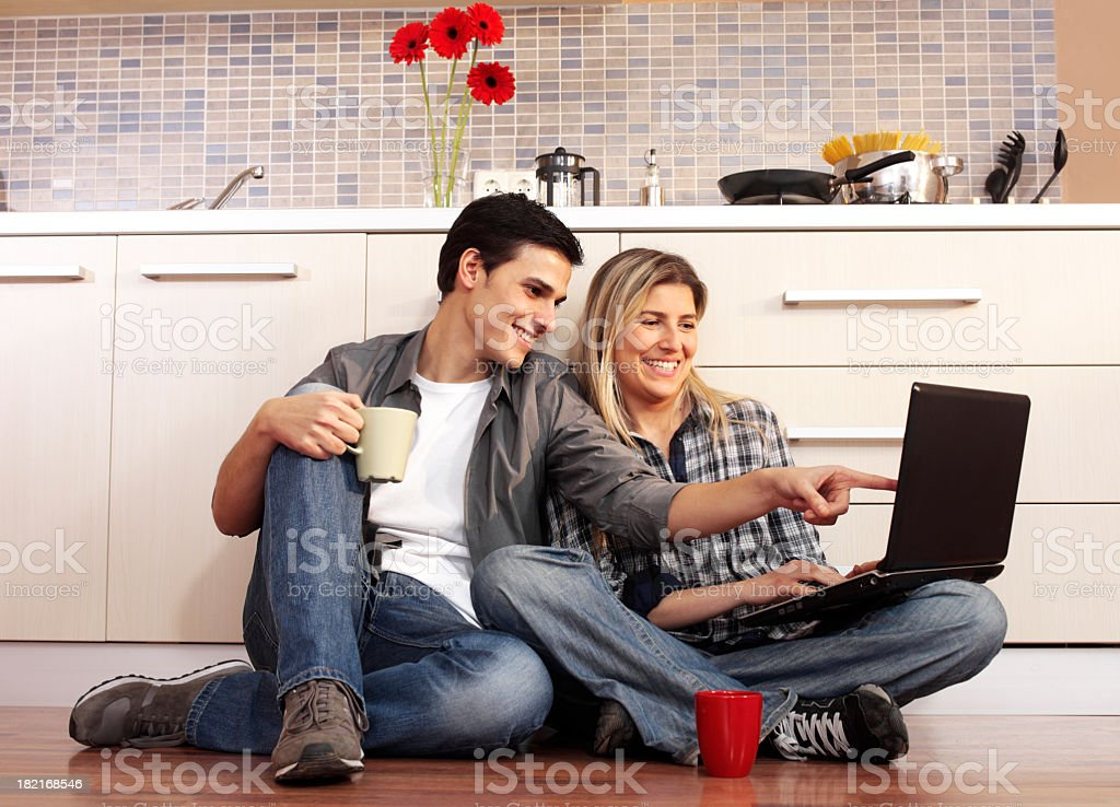 Couple using laptop computer in kitchen royalty-free stock photo