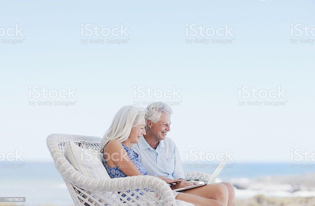 Couple using laptop on beach patio stock photo