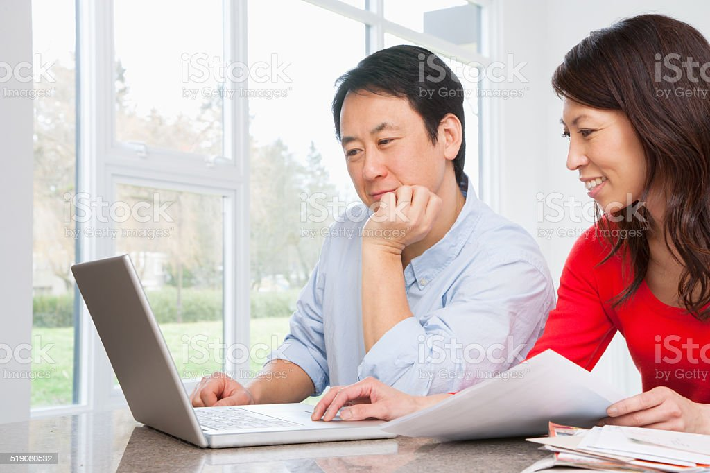 Couple using laptop to do finances stock photo