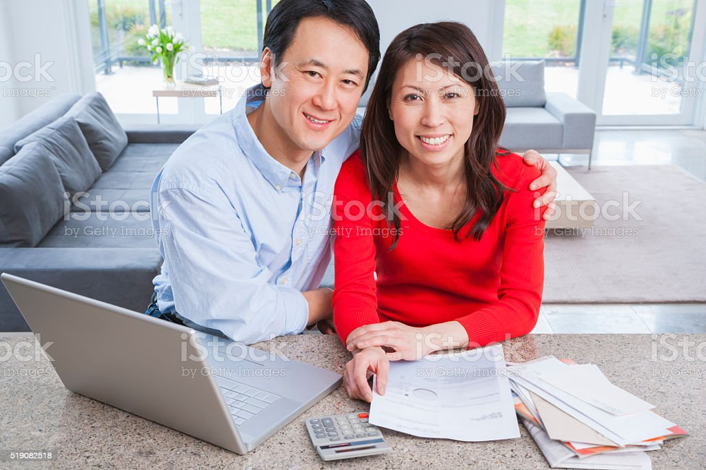 Couple using laptop to do finances stock photo