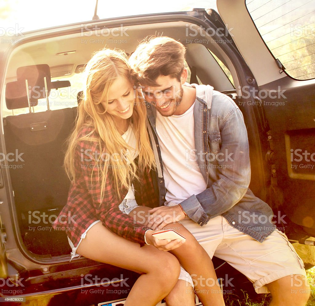 Couple Using Mobile Phone in a Car Trunk stock photo