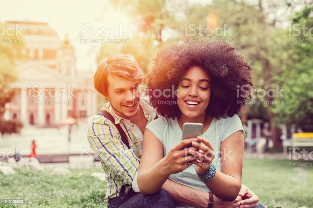 Couple using smartphone in the city park stock photo