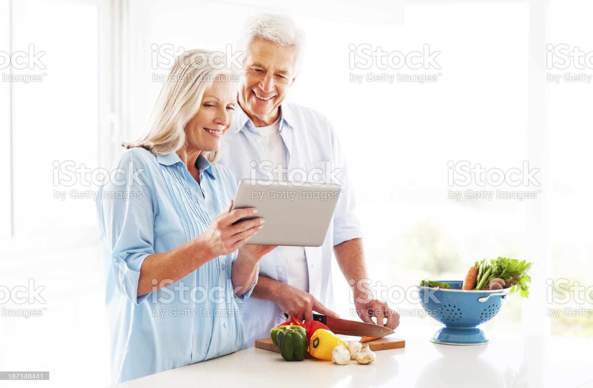 Couple Using Tablet Computer In Kitchen royalty-free stock photo