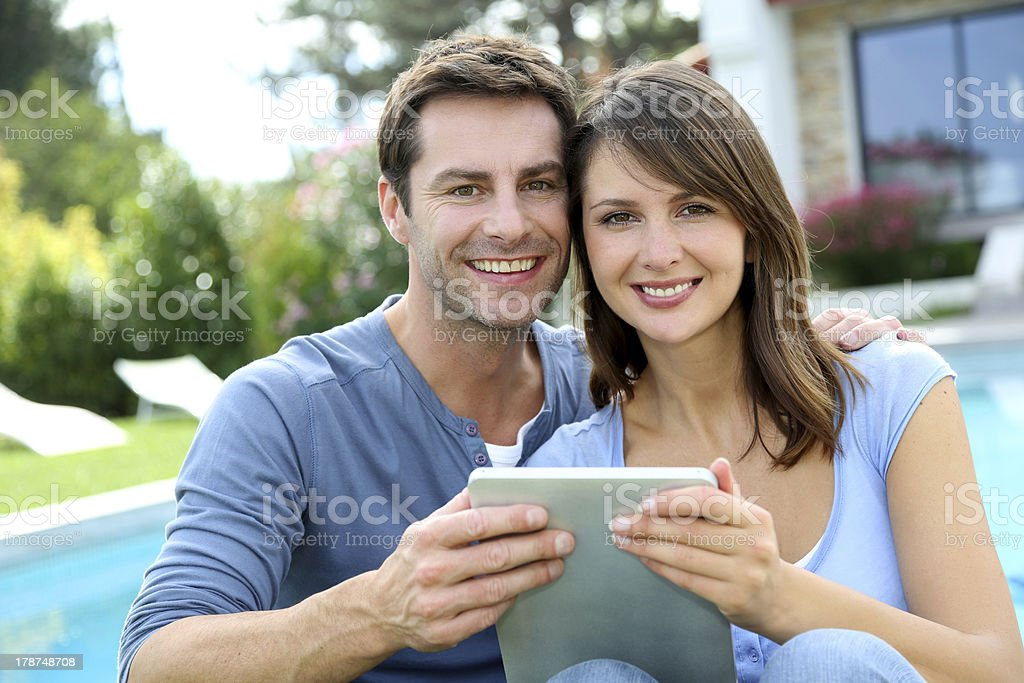 Couple using tablet in front of house royalty-free stock photo