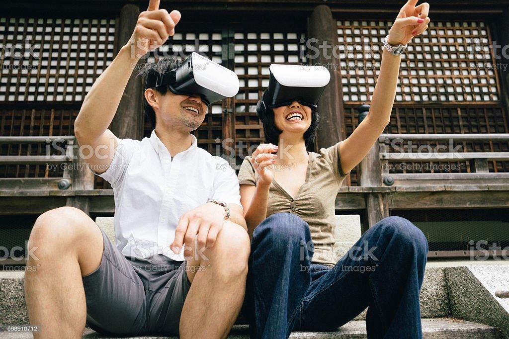 Couple using virtual reality simulator outdoors stock photo
