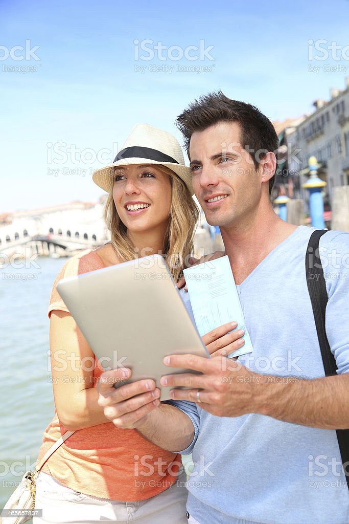 Couple visiting Venice with tablet and city map royalty-free stock photo