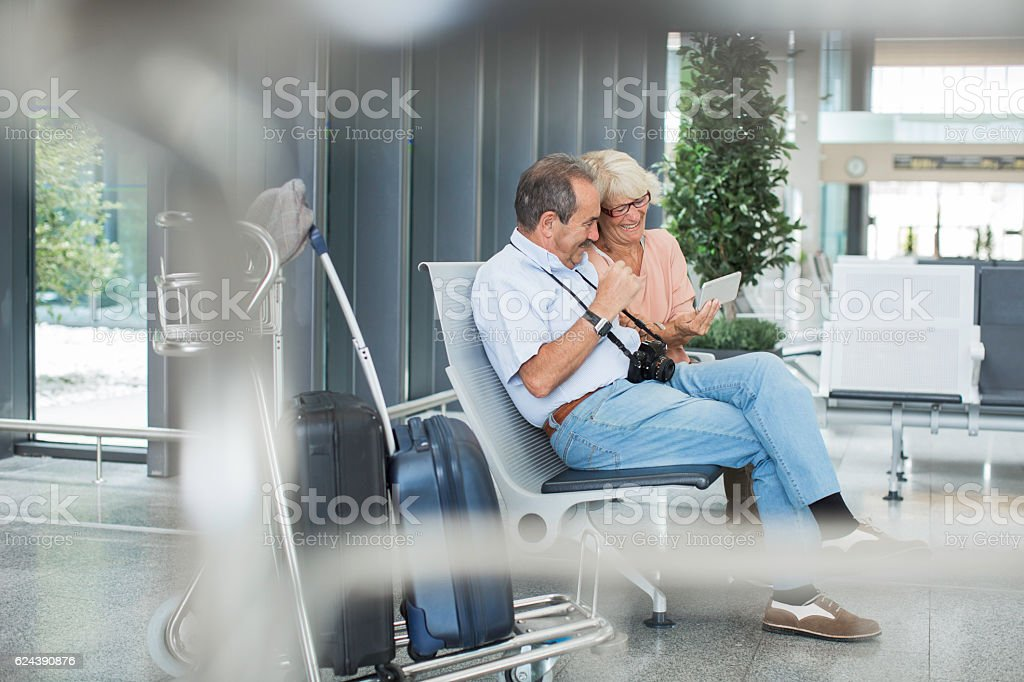 Couple waiting for plane departure and enjoying digital tablet. stock photo
