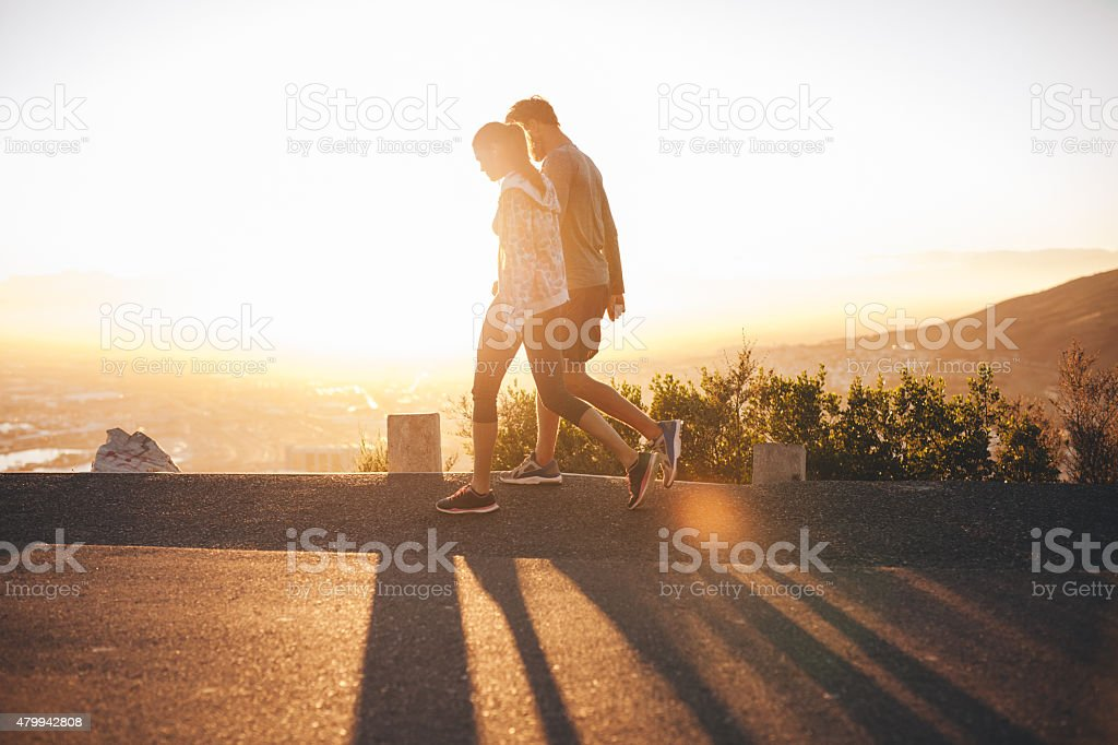 Couple walk along road at sunrise stock photo