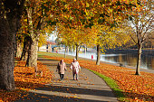Couple walk by the River Trent during Autumn.