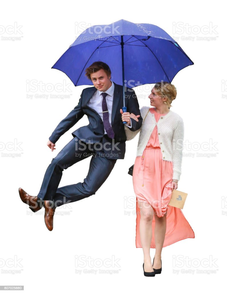 Couple walk in arm with umbrella and male jumps stock photo