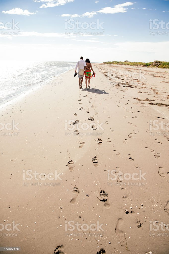 Couple walkind down the beach stock photo