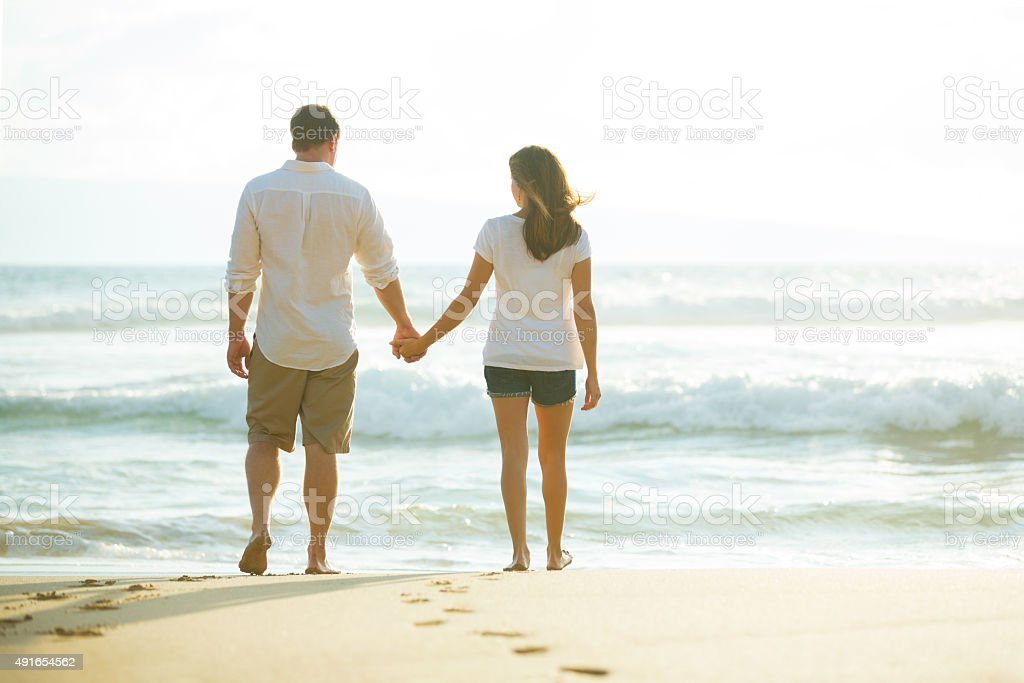 Couple Walking along the Ocean at Sunset stock photo