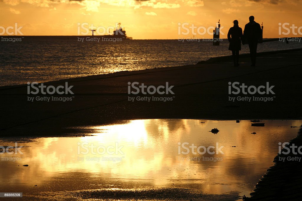 couple walking along the promenade at sunset stock photo