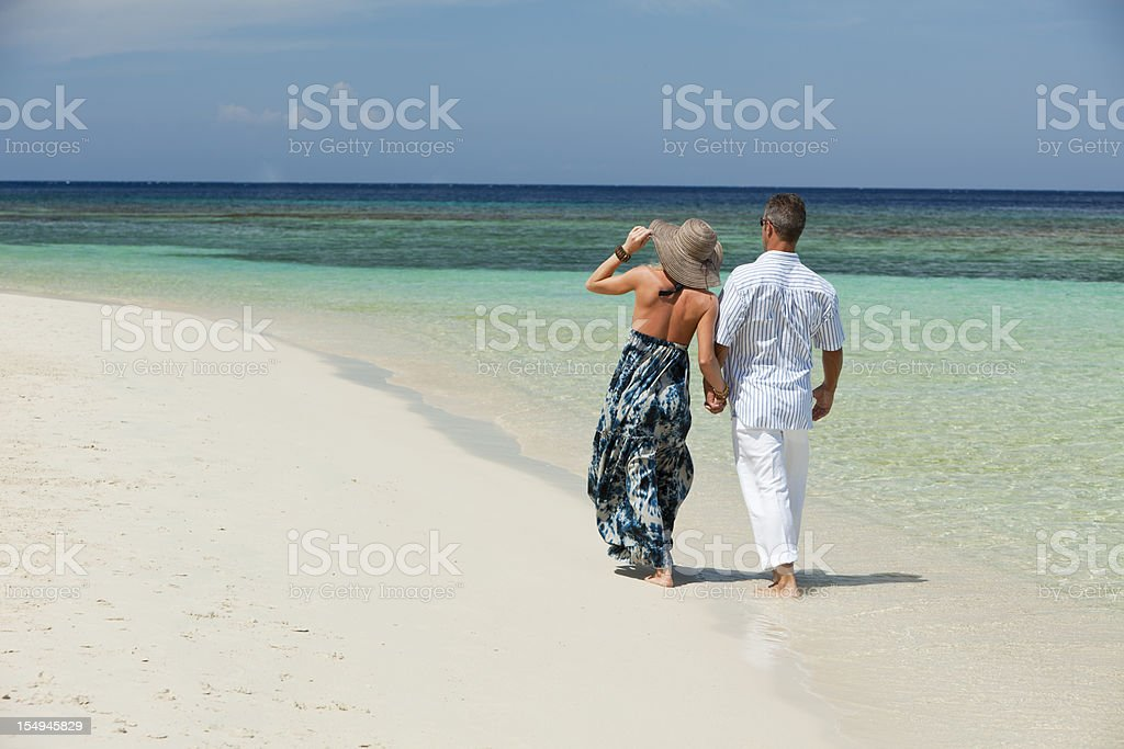 Couple walking along tropical beach royalty-free stock photo