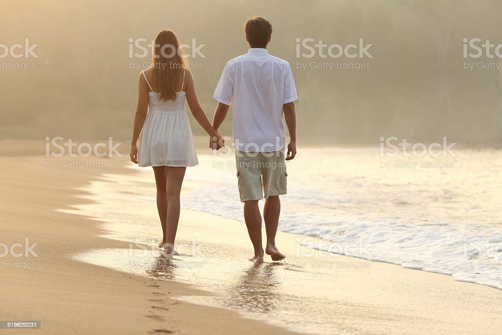 Couple walking and holding hands on the sand stock photo