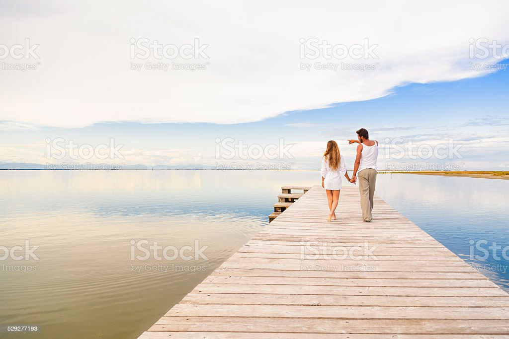 Couple walking and pointing to the horizon stock photo