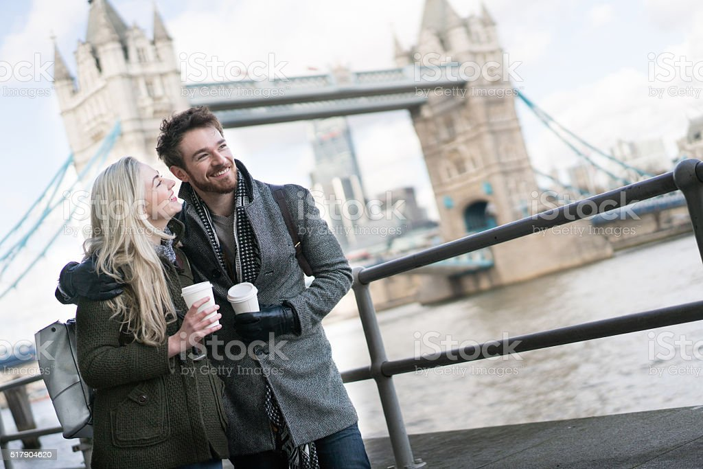 Couple walking around London drinking coffee to go stock photo