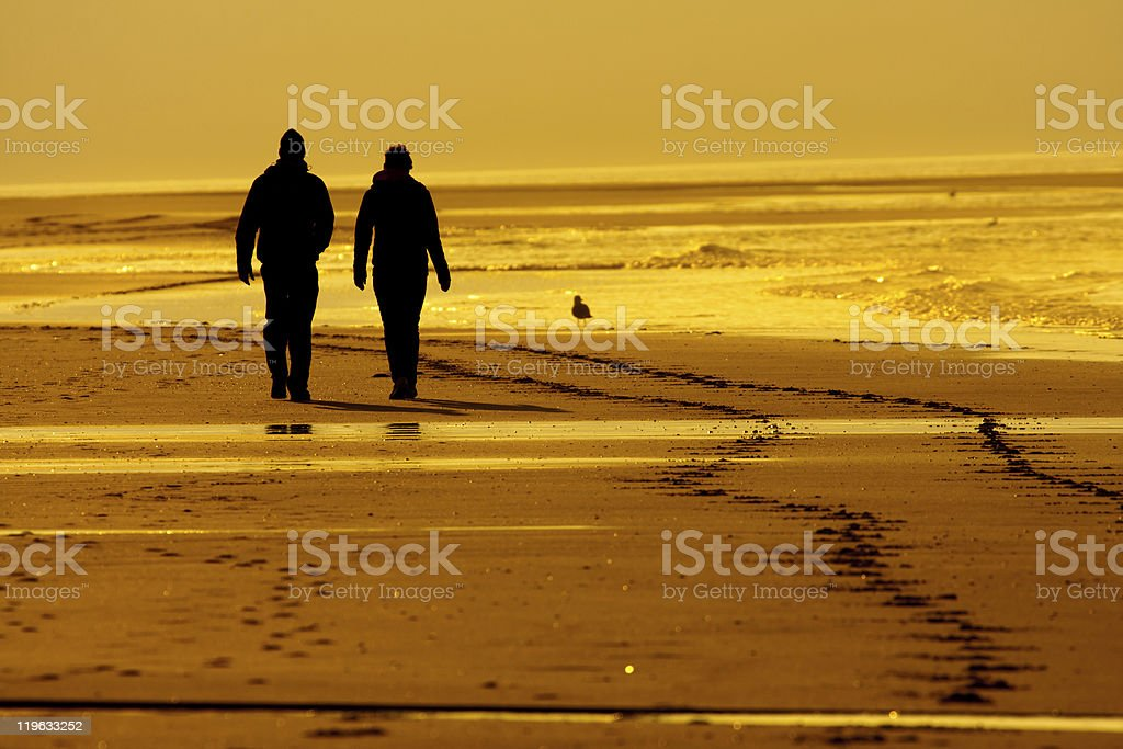 couple walking at a beach in the evening sun stock photo