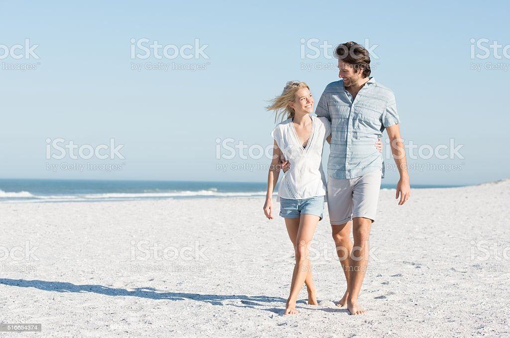 Young couple embracing and walking at the beach on a bright sunny...
