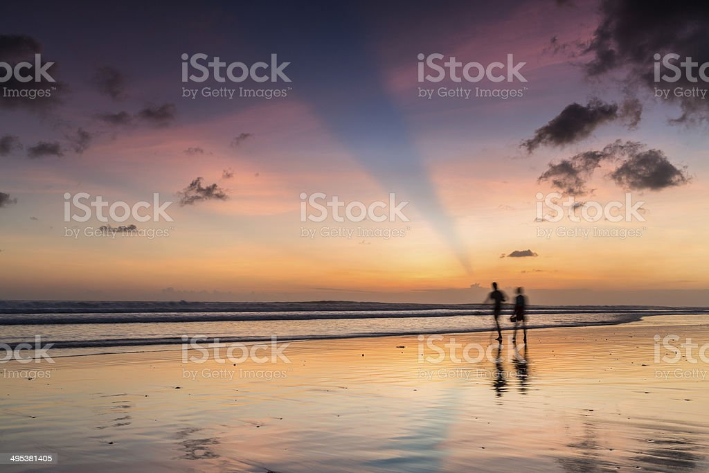 Couple walking at sunset on the beach stock photo