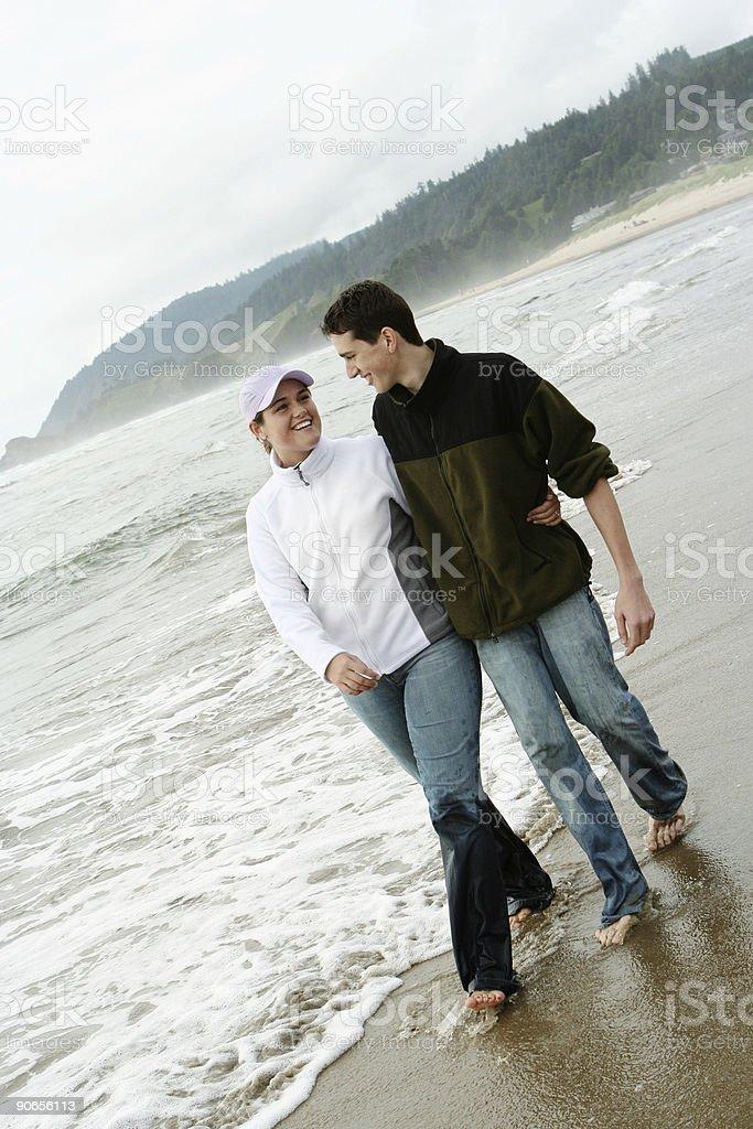 Couple Walking Barefoot Along the Beach royalty-free stock photo