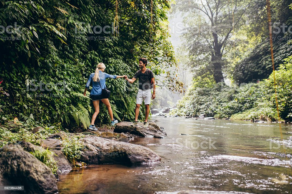 Couple walking by stream in forest stock photo