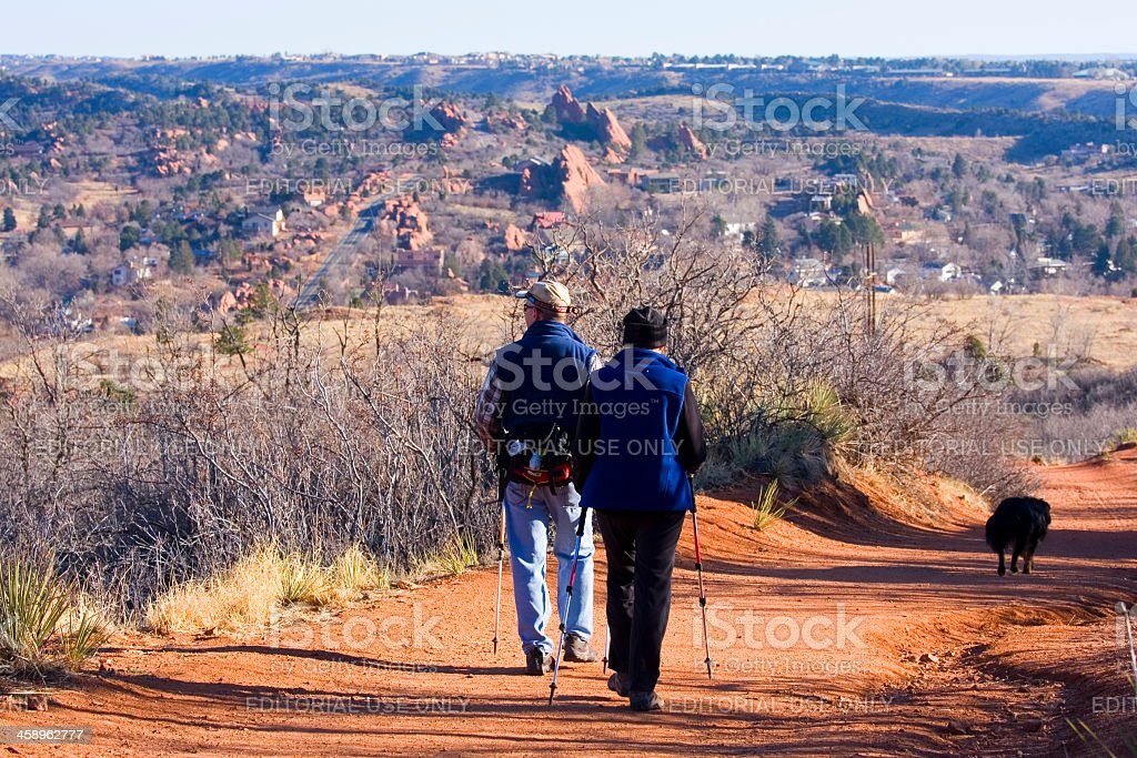 Couple Walking Dog in Red Rocks Open Space royalty-free stock photo